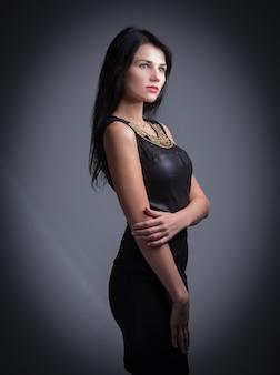 Piękna kobieta z czerwonymi ustami w małej czarnej sukience