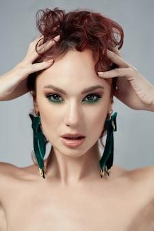 Piękna kobieta z czerwonymi włosami i zielonymi kolczykami