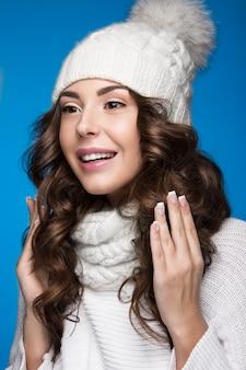 Piękna kobieta z delikatnym makijażem, designerskim manicure i uśmiechem w białej dzianinowej czapce