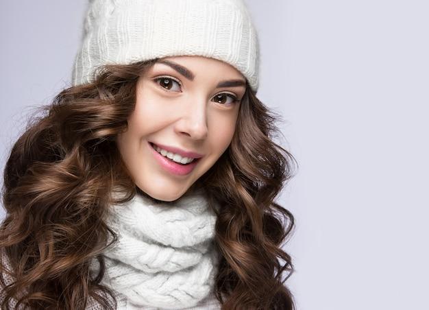 Piękna kobieta z delikatnym makijażem, lokami i uśmiechem w białej dzianinowej czapce