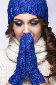 Piękna kobieta z delikatnym makijażem, lokami i uśmiechem w niebieskiej czapce z dzianiny