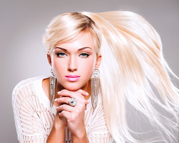 Piękna kobieta z długimi, białymi włosami i jasnym makijażem mody.
