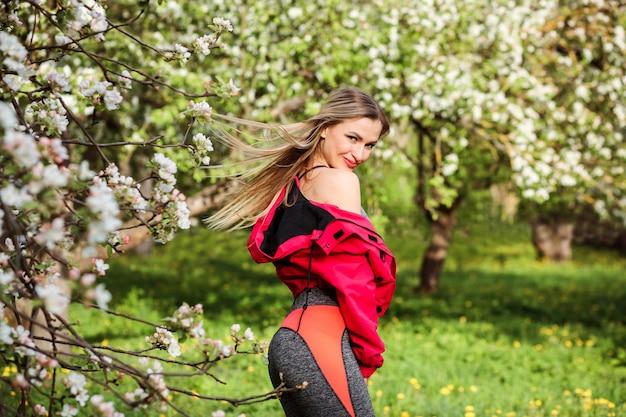 Piękna kobieta z długimi blond włosami pozuje wśród kwitnących drzew. atrakcyjna kobieta ubrana jest w jasnoróżową bomberkę i szare rajstopy. słoneczny wiosenny dzień, na zewnątrz.