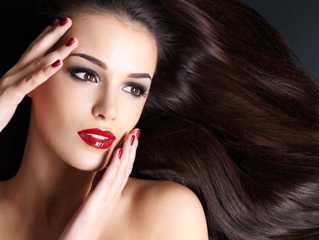 Piękna kobieta z długimi brązowymi prostymi włosami i czerwonymi paznokciami leżącego