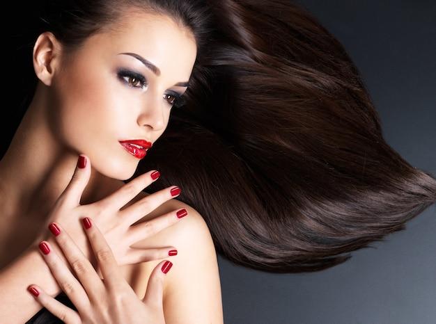 Piękna kobieta z długimi brązowymi prostymi włosami i czerwonymi paznokciami leżącymi na ciemnej ścianie