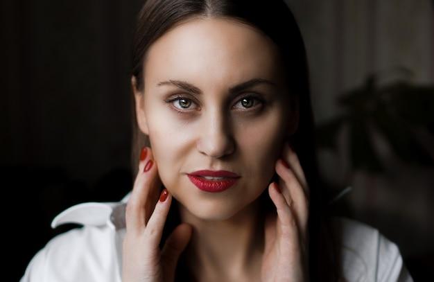 Piękna kobieta z długimi brązowymi prostymi włosami i czerwonymi paznokciami naturalny portret domu