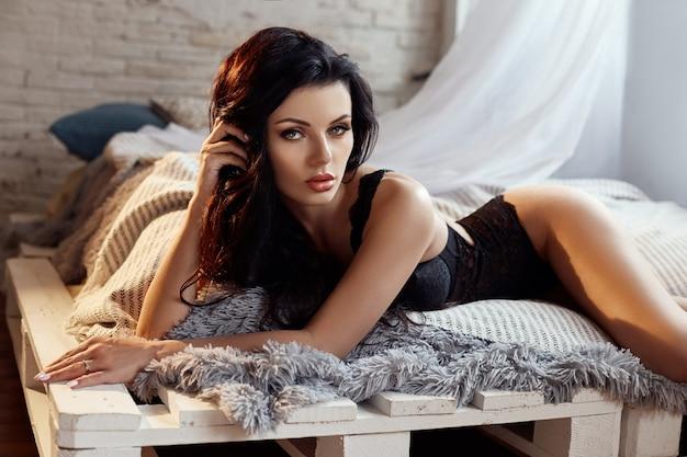 Piękna kobieta z długimi czarnymi włosami siedzi na łóżku w czarnej bieliźnie. idealne ciało gładka czysta skóra. dziewczyna czeka wieczorem na ukochaną osobę na łóżku