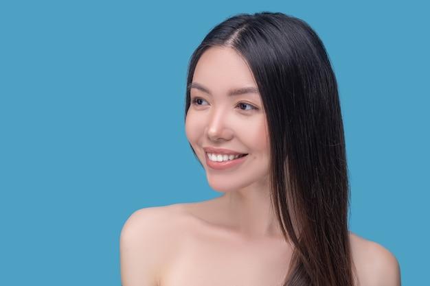 Piękna kobieta z długimi i zdrowymi włosami ładnie się uśmiecha