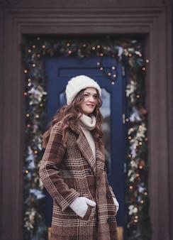 Piękna kobieta z długimi kręconymi włosami w ciepłych zimowych ubraniach
