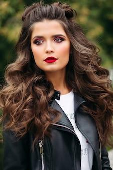 Piękna kobieta z długimi kręconymi włosami w skórzanej kurtce.