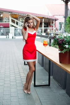 Piękna kobieta z długimi nogami w czerwonej sukience rozmawia przez telefon