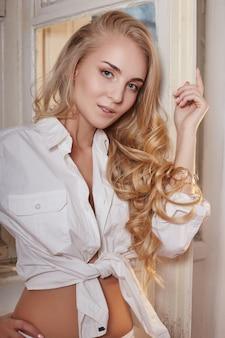 Piękna kobieta z długimi włosami farbowanie w ultra blond, naturalnym makijażu. stylowe loki fryzury wykonane w salonie kosmetycznym. blondynka moda