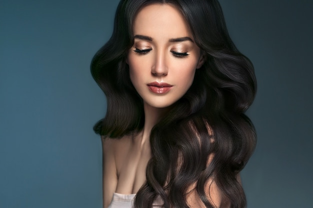 Piękna kobieta z długimi włosami, połysk i kręcone, piękna dziewczyna kobieta na darl szarym tle. strzał studio.