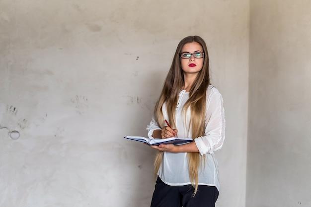 Piękna kobieta z długimi włosami, trzymając notatnik i ołówek