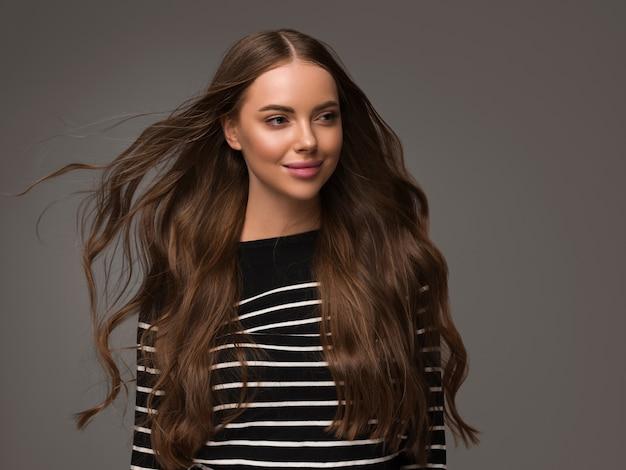 Piękna kobieta z długimi zdrowymi kręconymi włosami w dorywczo pasiasty sweter. kolor tła.