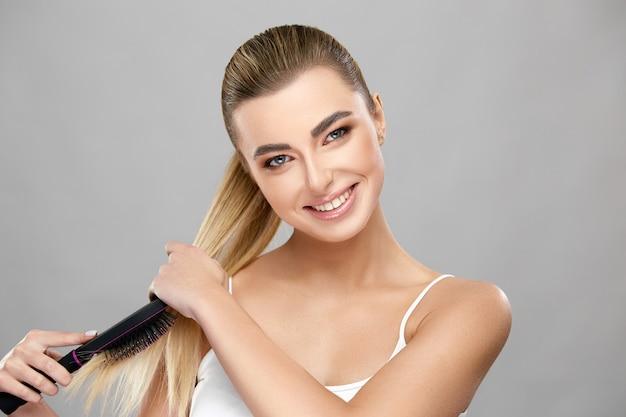 Piękna kobieta z długimi zdrowymi włosami blondy za pomocą pędzla i uśmiechając się do kamery na szarej ścianie, pielęgnacja włosów z sexy blond model
