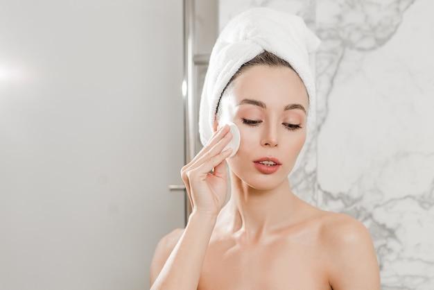 Piękna kobieta z doskonałej skóry robi makijaż i czyszczenie jej skóry na twarzy