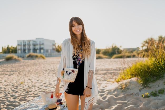 Piękna kobieta z falującymi włosami brunetki, ubrana w białą zasłonę boho patrzy w kamerę z uśmiechem. pozowanie na plaży w pobliżu hotelu. kolory zachodu słońca.