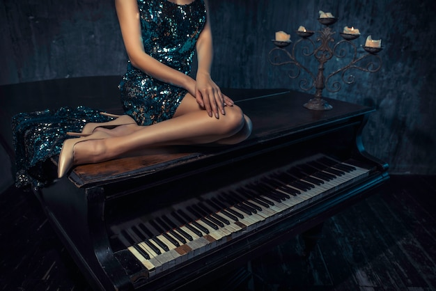 Piękna kobieta z fantazyjną elegancką suknią pozowanie w sali fortepianu