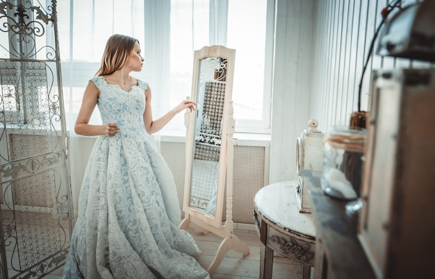Piękna kobieta z fantazyjną suknią ślubną przygotowuje się do imprezy
