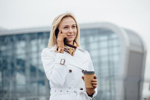 Piękna kobieta z filiżanką blisko budynku biurowego.
