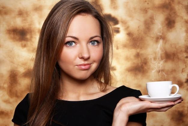 Piękna kobieta z filiżanką gorąca kawa
