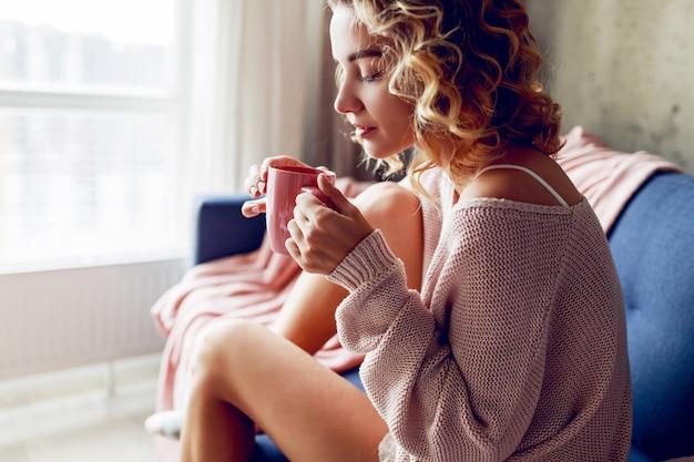 Piękna kobieta z filiżanką kawy na kanapie