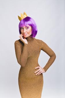 Piękna kobieta z fioletową fryzurą w luksusowej sukience. ma złotą koronę, uśmiechnięta