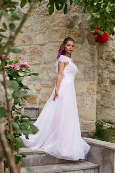 Piękna kobieta z fioletowymi włosami w białej sukni ślubnej spaceruje po ogrodzie. naturalny makijaż