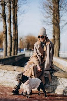Piękna kobieta z francuskiego buldoga odprowadzeniem w parku