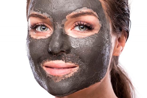 Piękna kobieta z glinianą lub borowinową maską na twarzy