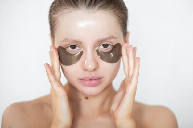 Piękna kobieta z hydrożelowymi łatami na oczy na twarzy