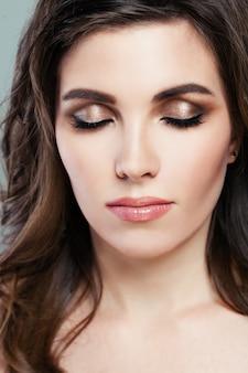 Piękna kobieta z idealnym makijażem. brązowy cień do powiek i naturalne różowe usta. zbliżenie twarzy