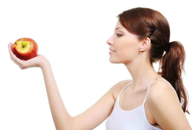 Piękna kobieta z jabłkiem na białym tle