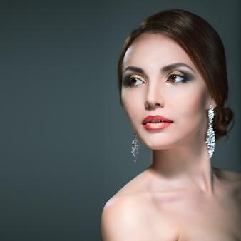 Piękna kobieta z jasnym makijażem na szarym tle