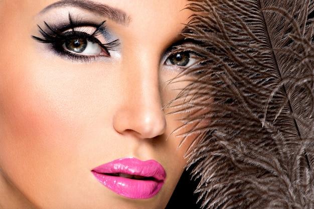 Piękna kobieta z jasnym profesjonalnym makijażem z piórami w pobliżu twarzy.