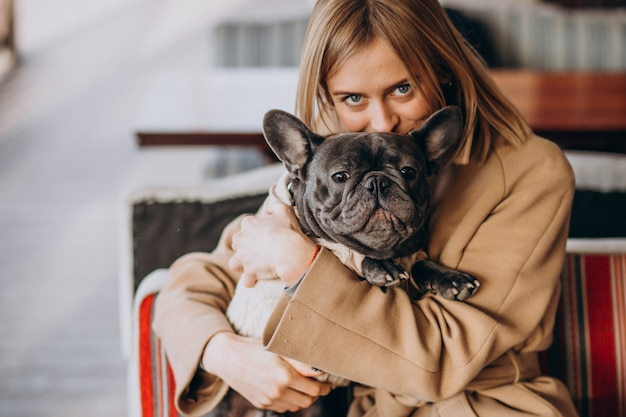 Piękna kobieta z jej ślicznym francuskim buldogiem w ciepłym stroju