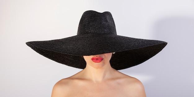 Piękna kobieta z kapeluszem i czerwonymi wargami. moda retro