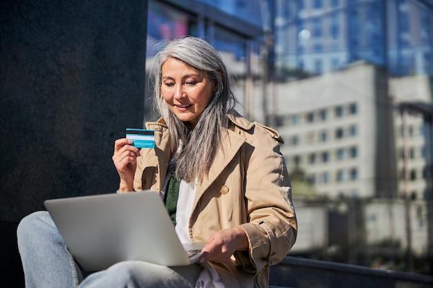 Piękna kobieta z kartą kredytową za pomocą laptopa na zewnątrz