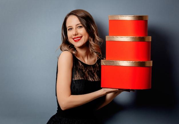 Piękna kobieta z kierowym kształta pudełkiem na szarości ścianie