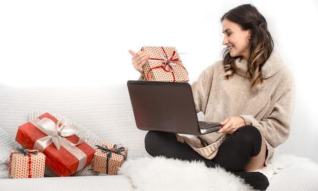 Piękna kobieta z komputerem i prezentami bożonarodzeniowymi.