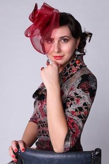 Piękna kobieta z koralowymi kolczykami i czerwonym kapeluszem