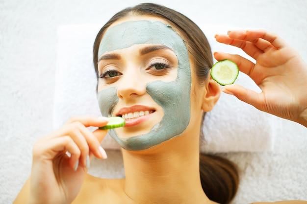 Piękna kobieta z kosmetyk maską na twarzy. dziewczyna dostaje leczenie w salonie spa. domowa maska na twarz. zabiegi spa.