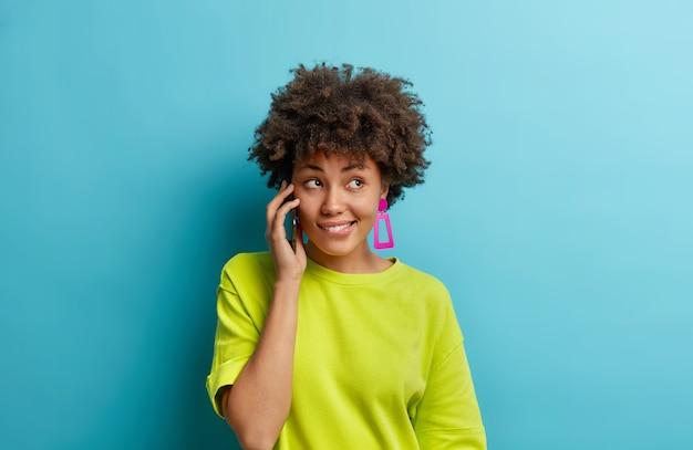 Piękna kobieta z kręconymi włosami rozmawia swobodnie z przyjacielem trzyma smartfon w pobliżu uszu gryzie usta patrzy w prawo cieszy się dobrą jakością urządzenia nosi casualową koszulkę odizolowaną na niebieskiej ścianie