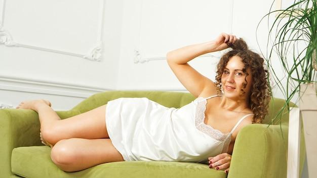 Piękna kobieta z kręconymi włosami w białej bieliźnie siedzi na zielonej kanapie w domu - szczęśliwy poranek