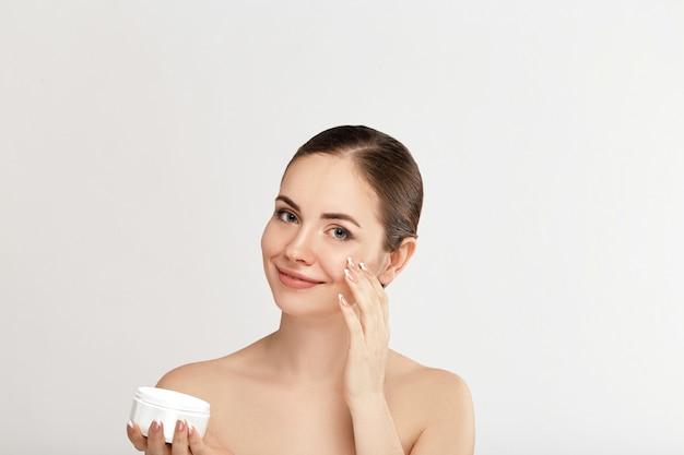 Piękna kobieta z kremem do twarzy. ochrona skóry. ochrona skóry. spa. młoda kobieta posiada krem nawilżający i uśmiechnięte. naturalny makijaż