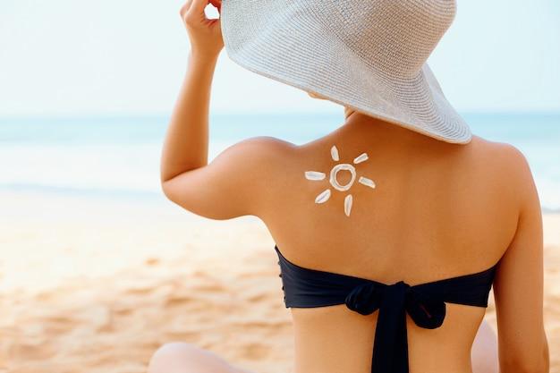 Piękna kobieta z kremem przeciwsłonecznym w kształcie słońca na plecach.