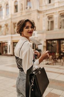 Piękna kobieta z krótką fryzurą w dżinsach, trzymając czarną torebkę w mieście. cudowna kobieta w koszuli z ciemnej koronki uśmiechnięta na ulicy.