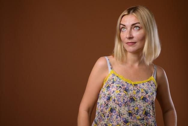 Piękna kobieta z krótkimi blond włosami z brązowego tyłu