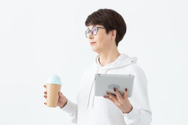 Piękna kobieta z krótkimi włosami, trzymając tabletkę i pijąc koktajl z zabawnego shakera